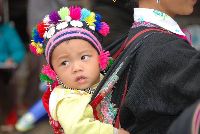Bébé Hmong dans le dos de sa maman