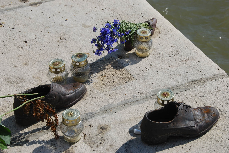 Chaussures, fleurs et bougies en hommage